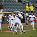 Michigan catcher Kendall Patrick, front, and closing pitcher Jacob Cronenworth celebrate a win in the NCAA Big Ten tournament championship college baseball game against Maryland, Sunday, May 24, 2015, in Minneapolis. Michigan won 4-3. (AP Photo/Hannah Foslien)