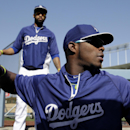 Los Angeles Dodgers' Yasiel Puig throws the ball in the dugout as teammate Matt Kemp, background left, walks down the steps before a baseball game against the Philadelphia Phillies on Tuesday, April 22, 2014, in Los Angeles The Associated Press
