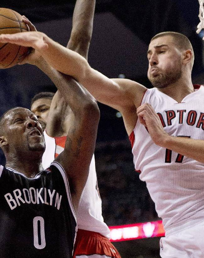 Brooklyn Nets forward Andray Blatche (0) drives to the hoop past Toronto Raptors center Jonas Valanciunas (17) during the second half of an NBA basketball game in Toronto on Tuesday, Nov. 26, 2013