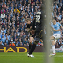 Manchester City's Samir Nasri, right, is partially obscured by the corner flag as he scores against Wigan during their English FA Cup quarterfinal soccer match at the Etihad Stadium, Manchester, England, Sunday, March 9, 2014