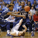The ball goes out-of-bounds off Butler guard Jackson Aldridge (11), bottom, as he goes for a loose ball with Georgetown guard D'Vauntes Smith-Rivera (4), left, and guard Jabril Trawick (55) in the first half of an NCAA college basketball game in Indianapolis, Tuesday, March 3, 2015. (AP Photo/Michael Conroy)