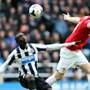 Newcastle United's Papaiss Cisse, left, eyes the ball with Manchester United's Phil Jones, right, during their English Premier League soccer match at St James' Park, Newcastle, England, Saturday, April 5, 2014