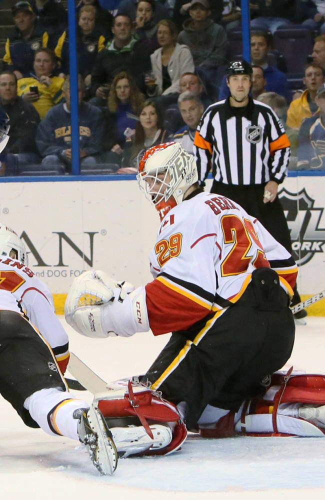 St. Louis Blues center Maxim Lapierre redirects the puck past Calgary Flames goaltender Reto Berra for his first goal as a Blues player, during the first period of an NHL hockey game Thursday, Nov. 7, 2013, in St. Louis. Calgary's Chad Billins is at center. The Flames won 3-2