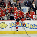 Chicago Blackhawks center Jonathan Toews, center, sits on the boards with his teammates as the ice is resurfaced for a shootout during an NHL hockey game against the Anaheim Ducks, Friday, Dec. 6, 2013, in Chicago. The Ducks won 3-2 The Associated Press