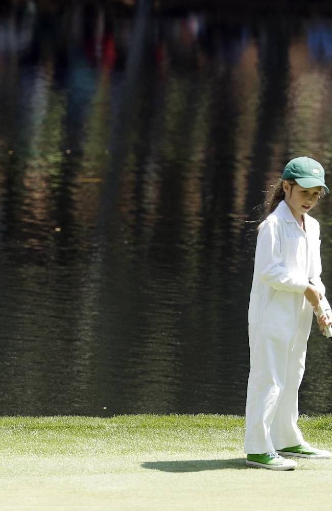 Phil Mickelson watches as his caddie Jim Mackay's daughter Emma putts during the par three competition at the Masters golf tournament Wednesday, April 9, 2014, in Augusta, Ga