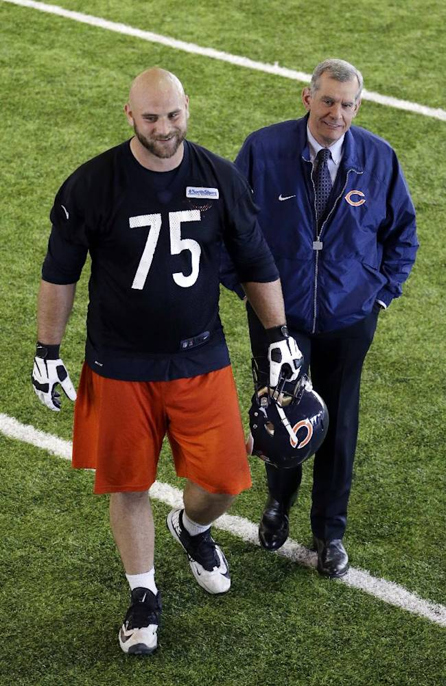 Chicago Bears general manager Phil Emery, right, walks with guard Kyle Long (75) after team's NFL football practice in Lake Forest, Ill., Wednesday, June 11, 2014