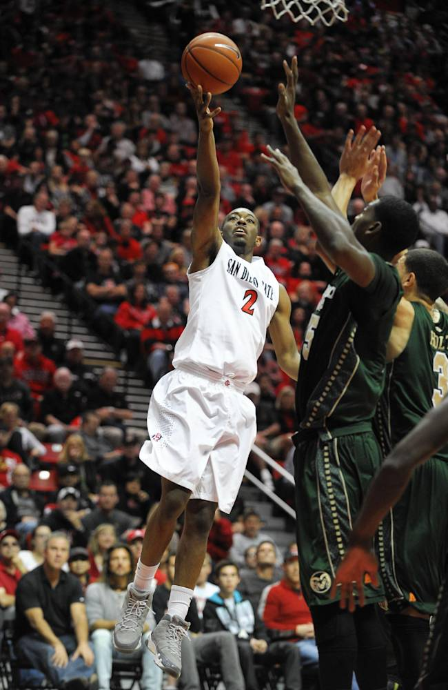 San Diego State's Xavier Thames (2) shoots over the defense of Colorado State's Gerson Santo (15) and Marcus Holt (3) during the first half of an NCAA college basketball game on Saturday, Feb. 1, 2014, in San Diego