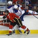 Edmonton Oilers Nail Yakupov, right, from Russia, checks Calgary Flames TJ Brodie during the third period of an NHL preseason hockey game in Calgary, Alberta, Sunday, Sept. 21, 2014 The Associated Press