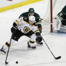 Boston Bruins left wing Brad Marchand (63) controls the puck in front of Minnesota Wild defenseman Jared Spurgeon (46) as Wild goalie Niklas Backstrom (32), of Finland, covers the net during the third period of an NHL hockey game in St. Paul, Minn., Wednesday, Dec. 17, 2014. The Bruins won 3-2 in overtime. (AP Photo/Ann Heisenfelt)