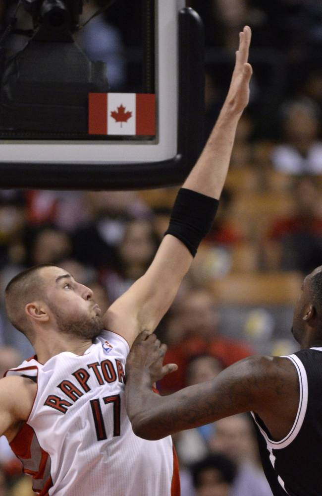Toronto Raptors' Jonas Valanciunas, left, of Lithuania, defends as Brooklyn Nets' Andray Blatche shoots during the first half of an NBA basketball game in Toronto on Tuesday, Nov. 26, 2013