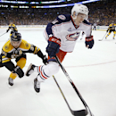Boston Bruins' Patrice Bergeron (37) and Columbus Blue Jackets' Matt Calvert (11) reach for the puck during the third period of an NHL hockey game in Boston, Saturday, Jan. 17, 2015. The Blue Jackets won 3-1 The Associated Press
