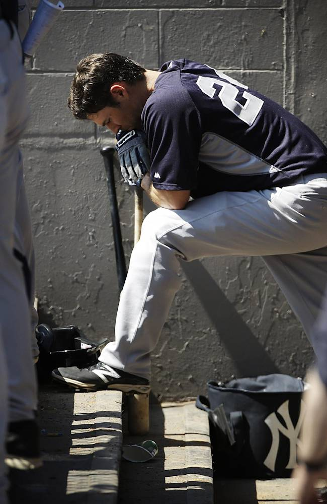 New York Yankees' Mark Teixeira waits to bat in the dugout in the sixth inning of an exhibition spring training baseball game against the Washington Nationals, Tuesday, March 11, 2014, in Viera, Fla