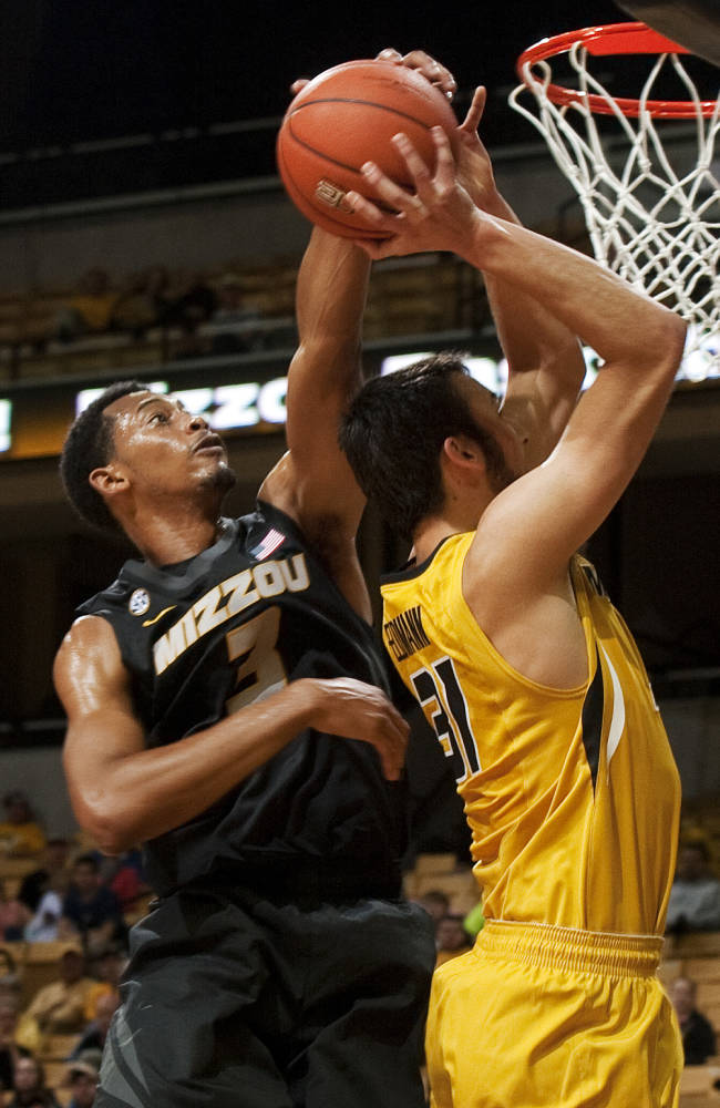 Missouri's Johnathan Williams, III, left, blocks the shot of Danny Feldmann, right, during an NCAA college basketball scrimmage Tuesday, Oct. 15, 2013, in Columbia, Mo