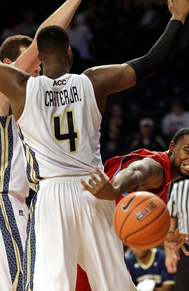 Delaware State's Jordan Lawson, right, passes the ball around the defense of Georgia Tech's Daniel Miller, left, and Robert Carter, Jr., during the first half of an NCAA college basketball game, Monday, Nov. 11, 2013, in Atlanta