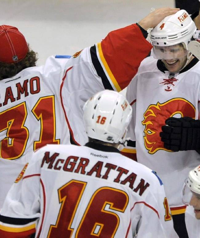 Calgary Flames' Kris Russell (4), celebrates with teammate Karri Ramo (31), of Finland, after scoring the winning goal to defeat the Chicago Blackhawks 3-2 in overtime of an NHL hockey game in Chicago, Sunday, Nov. 3, 2013