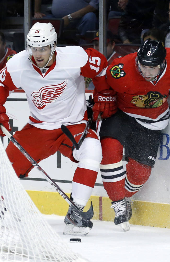 Detroit Red Wings center Riley Sheahan, left, and Chicago Blackhawks defenseman Nick Leddy battle for the puck behind the Blackhawks' net during the first period of an NHL preseason hockey game Tuesday, Sept. 17, 2013, in Chicago