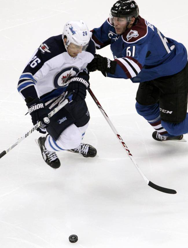 Colorado Avalanche defenseman Andre Benoit (61) pushes Winnipeg Jets right wing Blake Wheeler away from the puck during the first period of an NHL hockey game in Denver on Sunday, Dec. 29, 2013