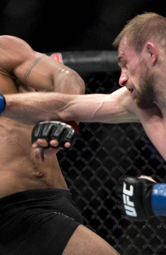 Demetrious Johnson, of the United States, ducks from a punch by Ali Bagautinov, of Russia, during the flyweight bout at UFC 174 in Vancouver, British Columbia, Saturday, June, 14, 2014
