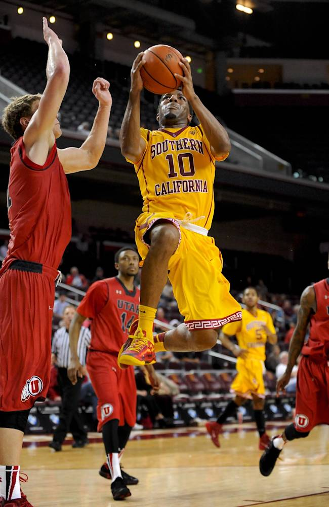 Southern California guard Pe'Shon Howard (10) gets by Utah center Dallin Bachynski, left, for a basket on a fast break during the second half of an NCAA college basketball game, Thursday, Feb. 13, 2014, in Los Angeles. Utah won 79-71