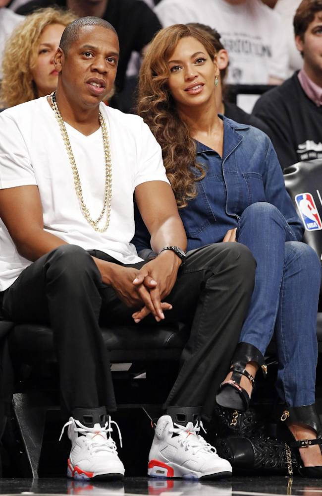 Entrepreneur and singer/songwriter Jay-Z, left, and his wife, singer Beyonce, watch Game 4 of the Brooklyn Nets second-round NBA playoff basketball game against the Miami Heat  at the Barclays Center, Monday, May 12, 2014, in New York