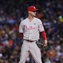 Philadelphia Phillies starting pitcher Kyle Kendrick waits to throw against the Colorado Rockies as a squirrel, which had been running around the field since the third inning, dashes past the mound in the fourth inning of a baseball game in Denver on Satu
