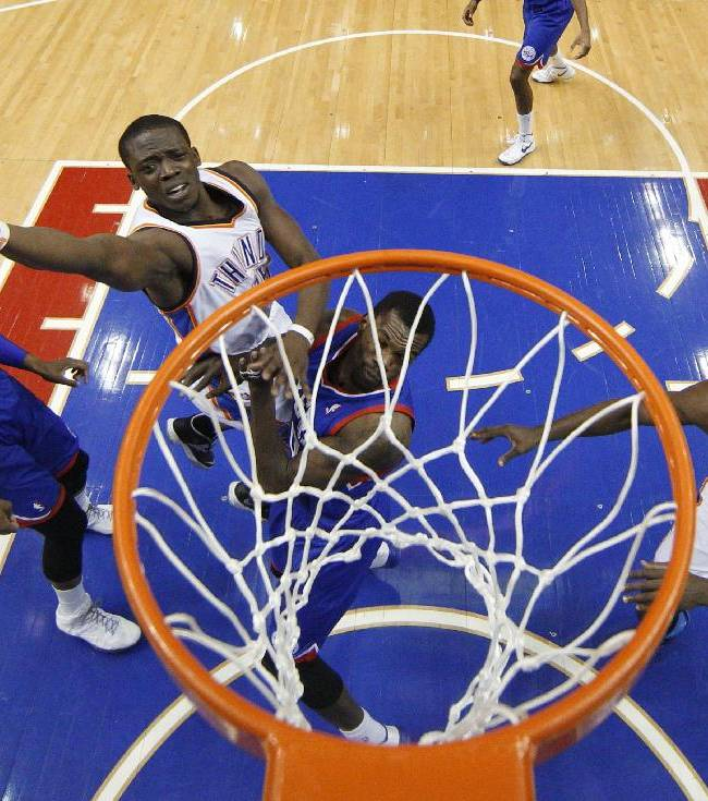 Oklahoma City Thunder's Reggie Jackson releases a shot next to Philadelphia 76ers' Dewayne Dedmon, center, with Lavoy Allen, left, and  Thunder's Serge Ibaka, right, nearby during the first half of an NBA basketball game, Saturday, Jan. 25, 2014, in Philadelphia