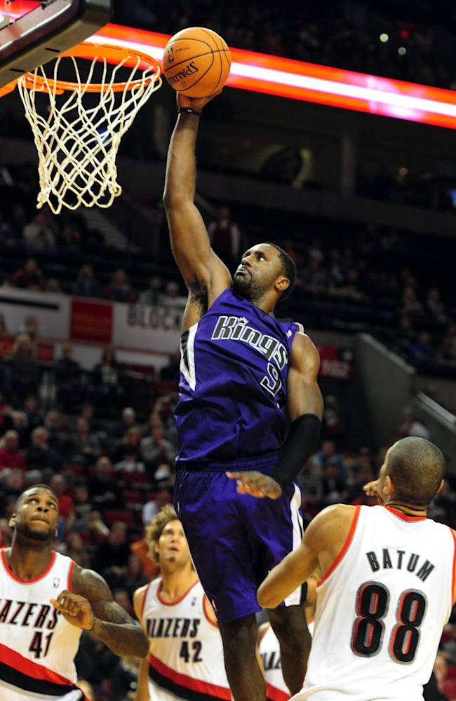 Sacramento Kings forward Patrick Patterson (9) dunks the ball on Portland Trail Blazers forward Thomas Robinson (41), Portland Trail Blazers center Robin Lopez (42) and Portland Trail Blazers forward Nicolas Batum (88) during the second half of an NBA basketball game Sunday, Oct. 20, 2013, in Portland. Portland won 109-105