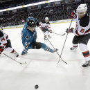 San Jose Sharks' Melker Karlsson, center, slips next to New Jersey Devils' Adam Henrique (14) and Andy Greene during the third period of an NHL hockey game Monday, Jan. 19, 2015, in San Jose, Calif. New Jersey won 5-2 The Associated Press