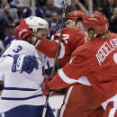 Detroit Red Wings' Jonathan Ericsson (52), of Sweden, gets hit in the face by Toronto Maple Leafs' Dion Phaneuf (3) as Detroit's Justin Abdelkader (8) tries to break up the fight during first period of an NHL hockey games Saturday, Oct. 18, 2014, in Detroit. (AP Photo/Duane Burleson)