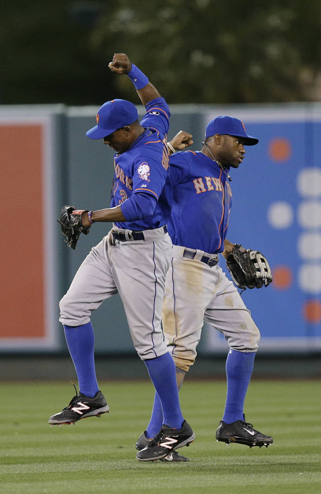 New York Mets' Curtis Granderson, left, and Eric Young Jr. celebrate their team's 7-6 win against the Los Angeles Angels after the 13th inning of a baseball game on Saturday, April 12, 2014, in Anaheim, Calif
