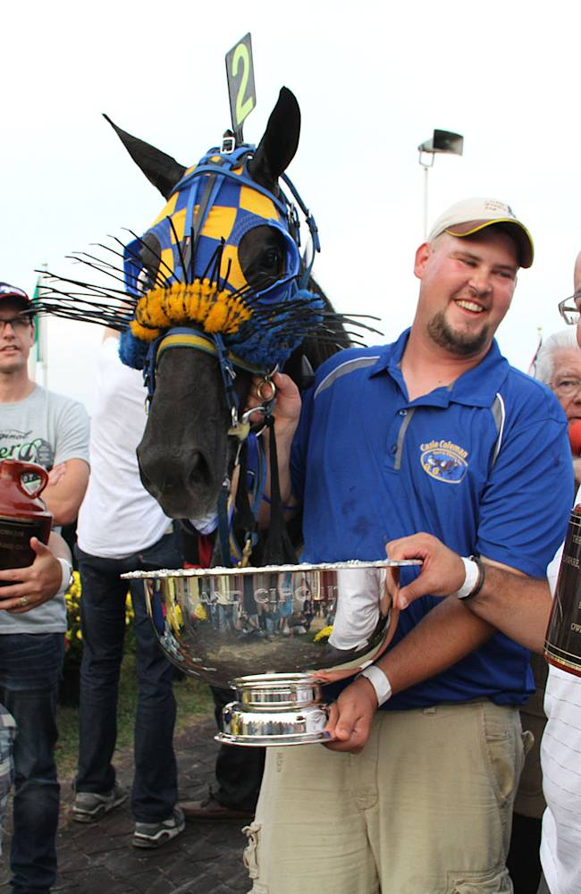 Co-owner Adriano Sorella, right, holds up a jug in the winner's circle along with trainer Cassie Coleman, left, and second trainer Boyd Wilson after Vegas Vacation won the Little Brown Jug harness race for three-year-old pacers at the Delaware County Fairgrounds in Delaware, Ohio, Thursday, Sept. 19, 2013