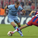 Manchester City's Edin Dzeko, left, and Bayern's Thomas Mueller challenge for the ball during the Champions League group E soccer match between Bayern Munich and Manchester City in Munich, Germany, Wednesday Sept.17,2014