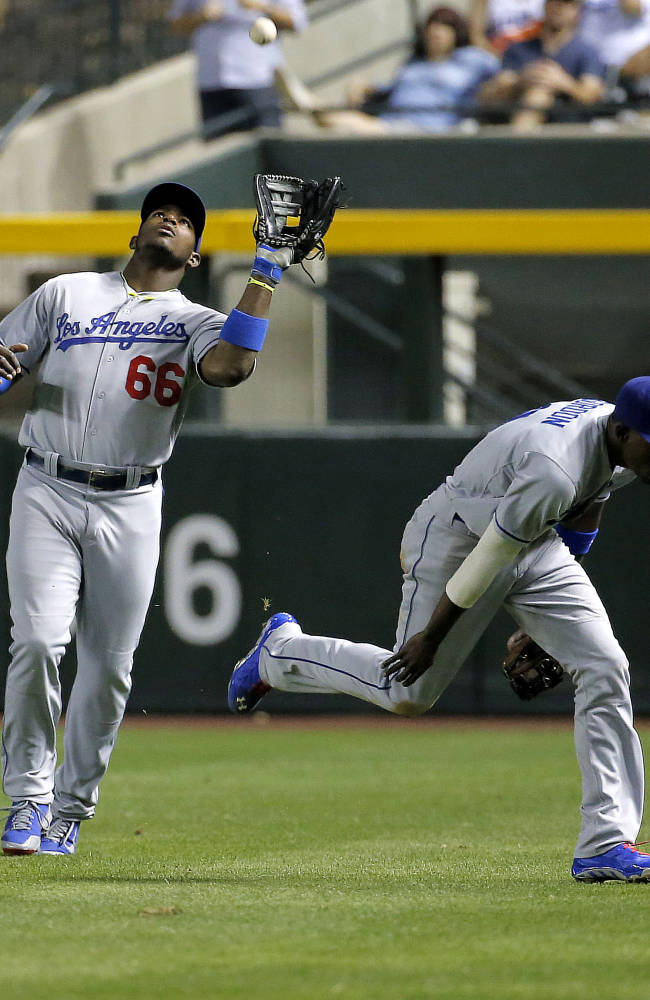 Los Angeles Dodgers' Yasiel Puig catches a fly out by Arizona Diamondbacks' Martin Prado as teammate Dee Gordon, right, ducks out of the way during the sixth inning of a baseball game on Friday, May 16, 2014, in Phoenix
