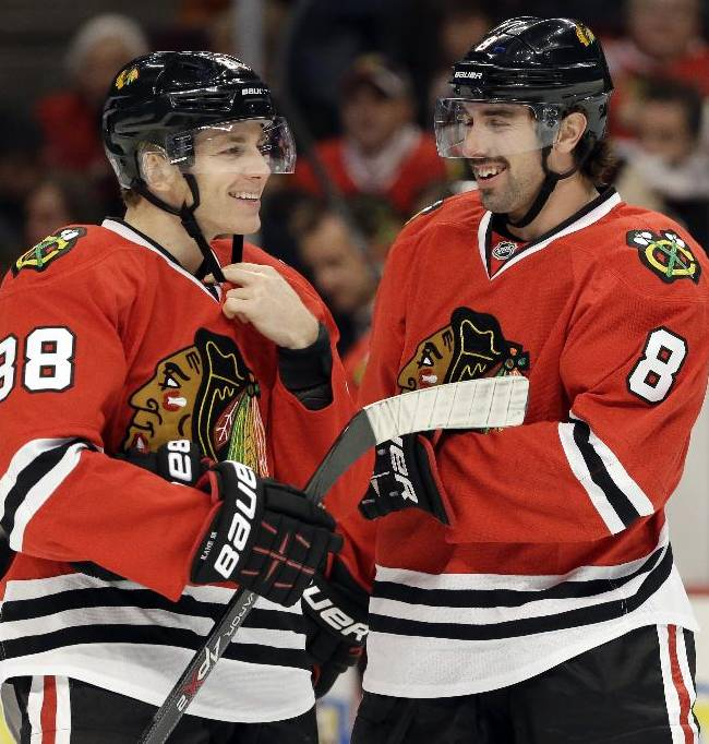 Chicago Blackhawks' Patrick Kane, left, smiles as he talks with Nick Leddy (8) during the first period of an NHL hockey game against the Phoenix Coyotes in Chicago, Thursday, Nov. 14, 2013