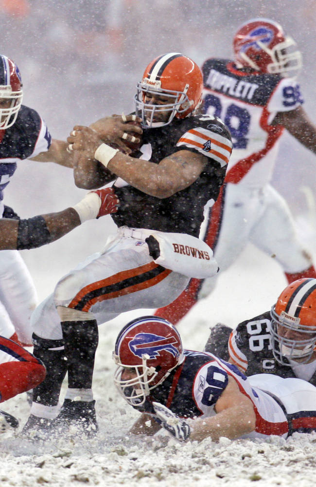 In this Dec. 16, 2007, file photo, Cleveland Browns running back Jamal Lewis, center, runs through the snow and Buffalo Bills defenders Angelo Crowell (55), Keith Ellison (56), Chris Kelsay (90) and Kyle Williams (95) for four yards in the fourth quarter of an NFL football game in Cleveland. Organizers of the first outdoor, cold-climate Super Bowl, in East Rutherford, N.J.,  have decided to embrace the snow as the game's unofficial theme. The 197-year-old Farmers' Almanac is already out with its forecast that a big winter storm will hit the area  that weekend
