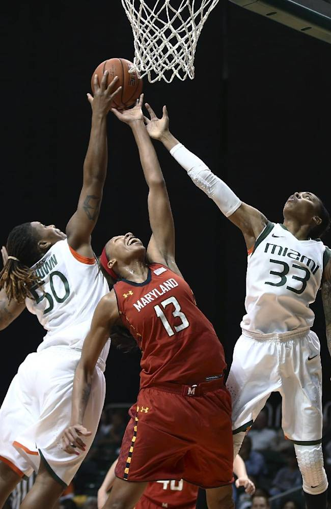 Miami's Maria Brown (50) blocks a shot by Maryland's Alicia DeVaughn (13) as Suriya McGuire (33) helps on defense during the second half of an NCAA college basketball game in Coral Gables, Fla., Thursday, Feb. 13, 2014. Maryland won 67-52