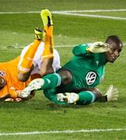 Houston Dynamo midfielder Ricardo Clark, left, tumbles over D.C. United goalkeeper Bill Hamid (28) during the first half of an MLS soccer match Saturday, March 2, 2013, in Houston. (AP Photo/Houston Chronicle,  Smiley N. Pool)