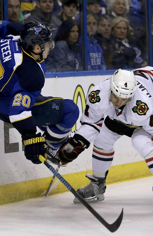 St. Louis Blues' Alexander Steen, left, is checked into the boards by Chicago Blackhawks' Niklas Hjalmarsson during the first overtime in Game 1 of a first-round NHL hockey Stanley Cup playoff series Thursday, April 17, 2014, in St. Louis