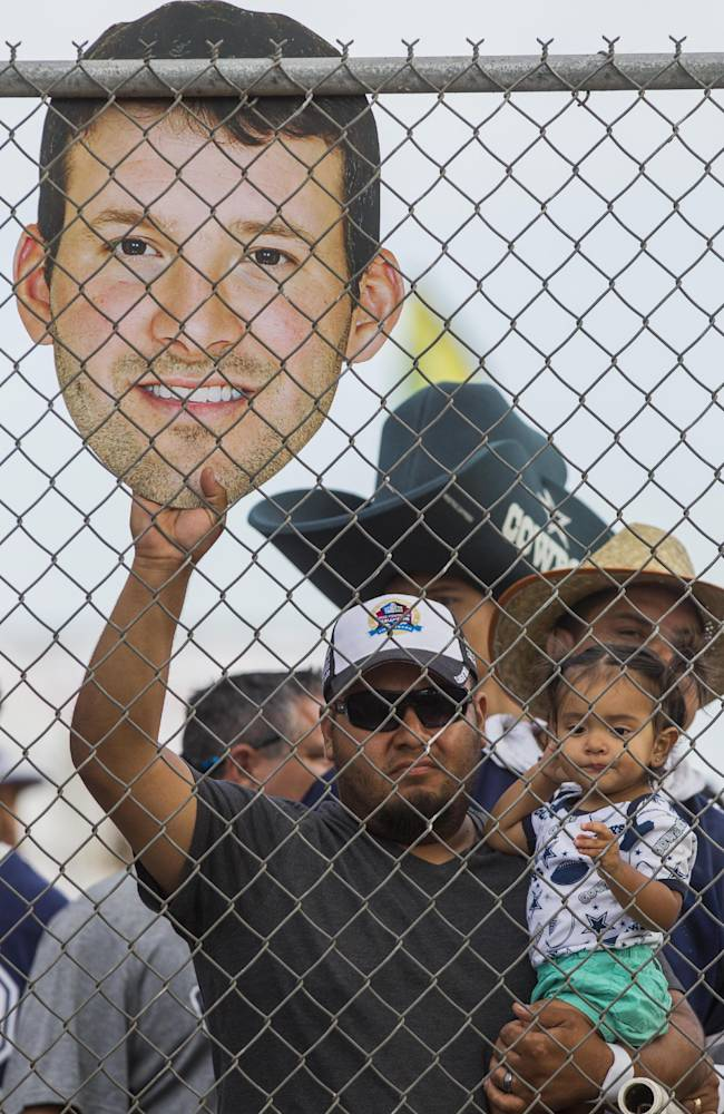 Fan Arnold Gomez of San Diego, with his daughter Victoria, holds a picture of Dallas Cowboys quarterback Tony Romo at NFL football training camp, Wednesday, July 30, 2014, in Oxnard, Calif