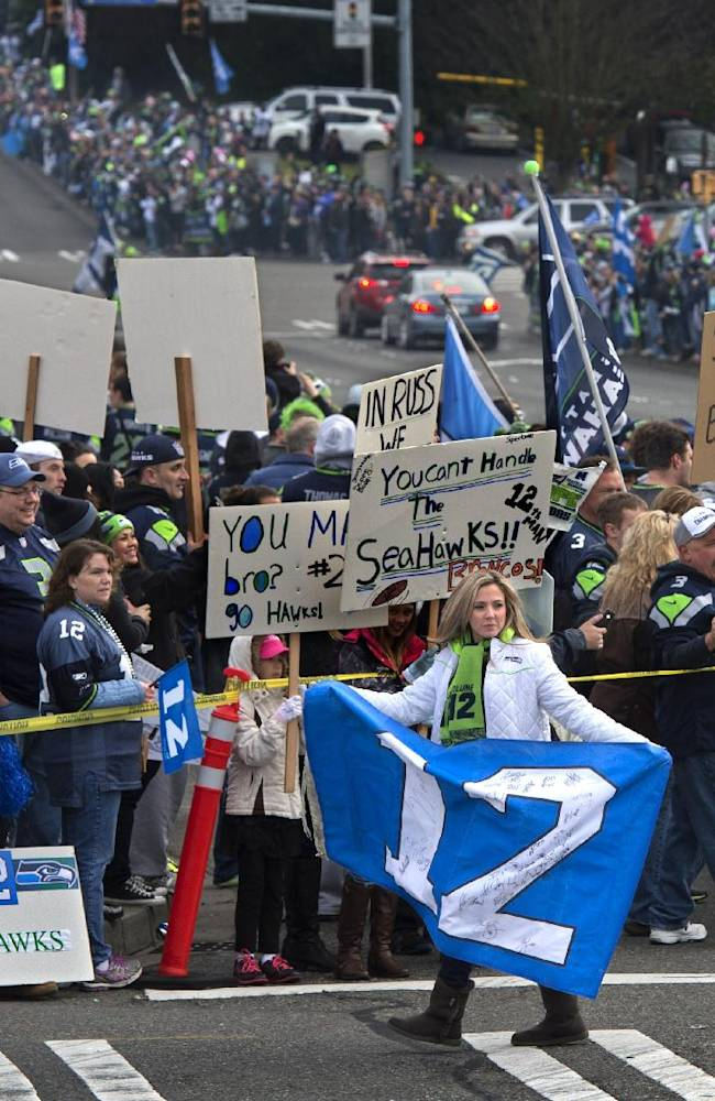 A woman carries a 12th man flag in front of Seahawk fans awaiting the Seahawks departure for the Super Bowl game, Sunday, Jan. 26, 2014, at Seatac, Wash. The Seahawks are scheduled to play the Denver Broncos in the NFL Super Bowl XLVIII football game, Sunday, Feb. 3 in East Rutherford, N.J