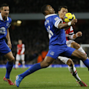 Everton's Sylvain Distin, centre, chests the ball as Arsenal's Mesut Ozil attempts to challenge during the English Premier League soccer match between Arsenal and Everton at the Emirates Stadium in London, Sunday, Dec. 8, 2013