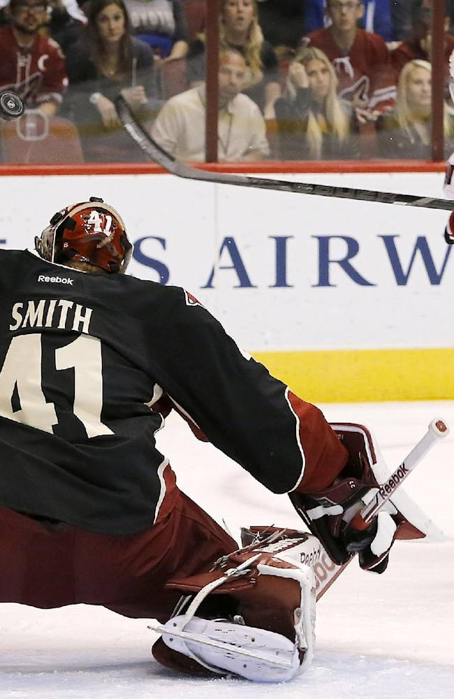 Phoenix Coyotes' Mike Smith (41) makes a save on a shot by Ottawa Senators' Kyle Turris, right, as official Gord Dwyer (19) watches during the first period in an NHL hockey game Tuesday Oct. 15, 2013, in Glendale, Ariz