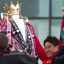 FILE - In this May 13, 2013 file photo, Manchester United's Shinji Kagawa, right, and Tom Cleverley hold the trophy outside Old Trafford Stadium as the team prepare to parade across Manchester after winning the English Premier League, Manchester, England. Manager Alex Ferguson will retire at the end of the season after more than 26 years in charge at the club. (AP Photo/Jon Super, File)