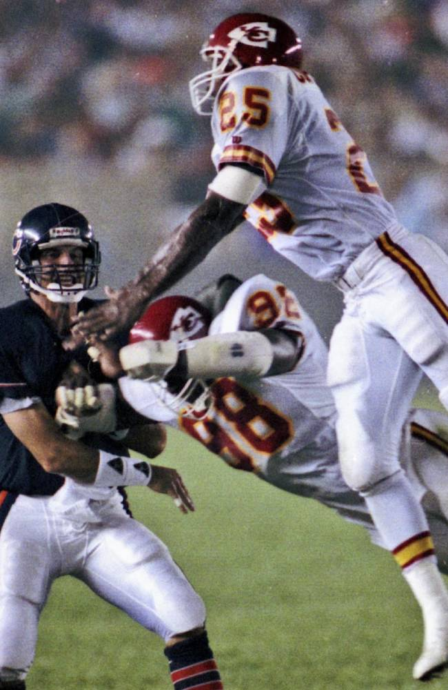 In this Aug. 28, 1989, file photo, Chicago Bears quarterback Jim Harbaugh, left, barely gets off a pass as Kansas City Chiefs Leonard Griffin (98) and Kevin Porter (25) apply pressure during the third quarter of an NFL football game in Chicago. Five former Chiefs players are suing the team, claiming it hid the risks of head injuries.  The plaintiffs in the lawsuit, filed Tuesday, Dec. 3, 2013, are Leonard Griffin, Chris Martin and his wife, Joe Phillips, Alexander Louis Cooper and Kevin Porter. All say they are suffering from brain damage, specifically chronic traumatic encephalopathy, or CTE