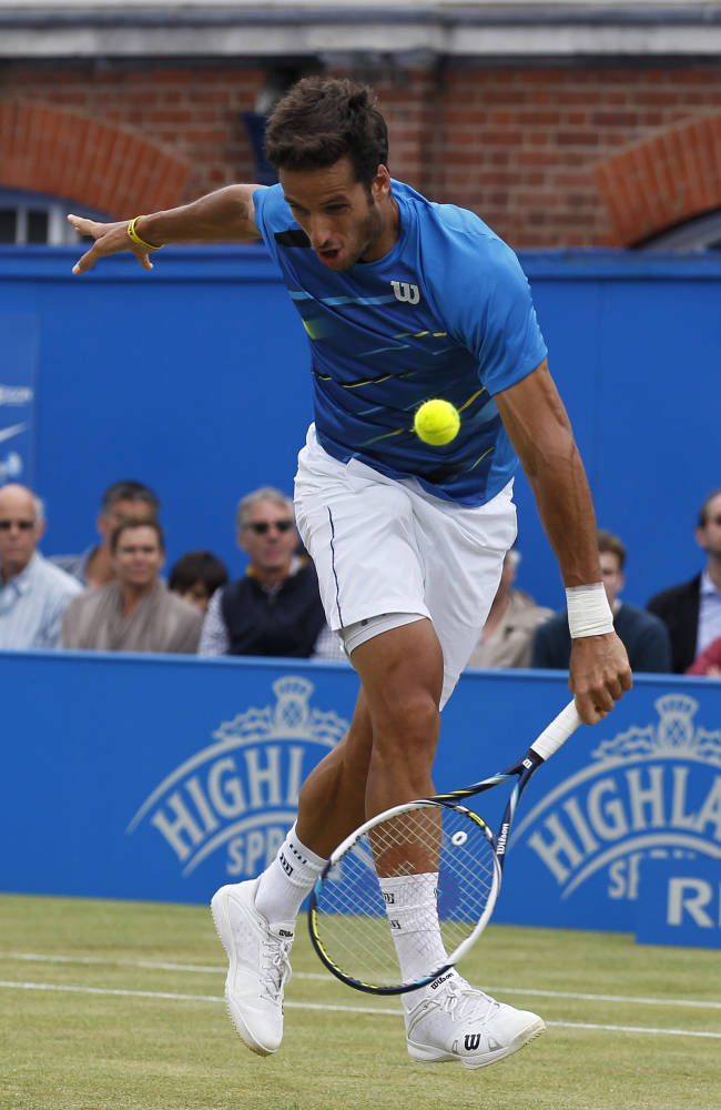 Feliciano Lopez of Spain plays a return to Grigor Dimitrov of Bulgaria, during their Queen's Club grass court championships singles final tennis match in London, Sunday, June 15, 2014