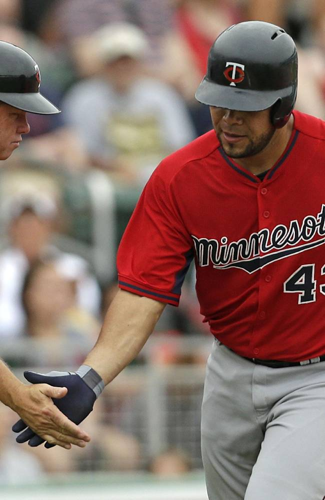 Minnesota Twins' Josmil Pinto (43) is greeted by third base coach Joe Vavra after hitting a home run during the seventh inning of an exhibition baseball game against the Boston Red Sox in Fort Myers, Fla., Saturday, March 29, 2014. The Twins won 7-4