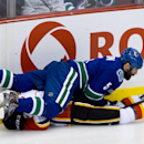 Vancouver Canucks' Jason Garrison, top, checks Calgary Flames' Paul Byron during the second period of an NHL hockey game, Saturday, March 8, 2014 in Vancouver, British Columbia The Associated Press