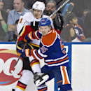 Calgary Flames' Mikael Backlund (11) is checked by Edmonton Oilers' Anton Lander (51) during second period NHL hockey action in Edmonton, Alberta., on Saturday Dec. 7, 2013 The Associated Press