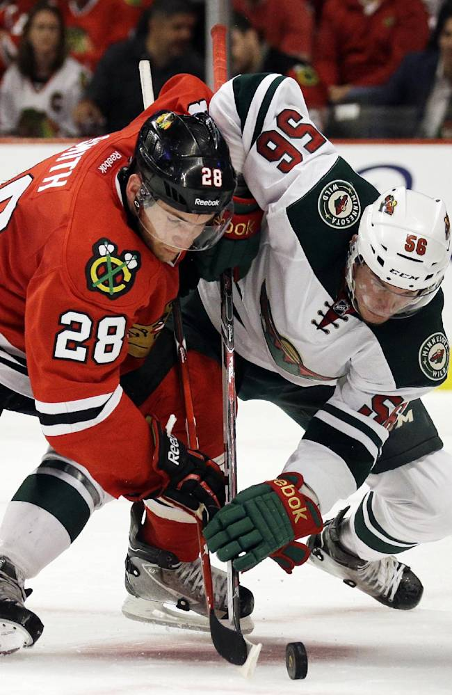 Chicago Blackhawks' Ben Smith (28) and Minnesota Wild's Erik Haula (56) battle for the puck during the second period in Game 1 of an NHL hockey second-round playoff series in Chicago, Friday, May 2, 2014