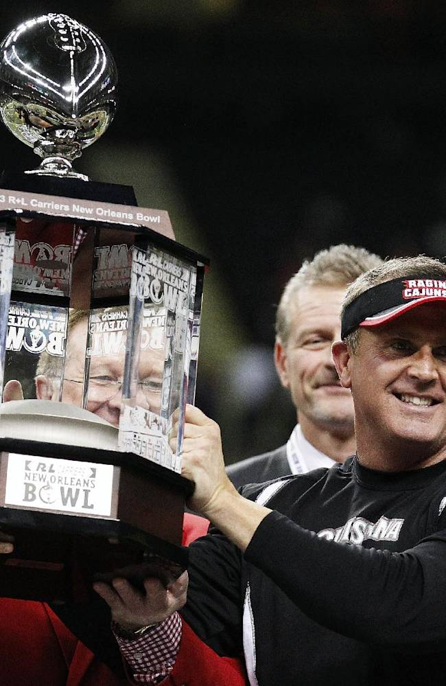 Louisiana-Lafayette head coach Mark Hudspeth holds the championship trophy after the New Orleans Bowl NCAA college football game, in New Orleans, Saturday, Dec. 21, 2013. Louisiana-Lafayette defeated Tulane 24-21